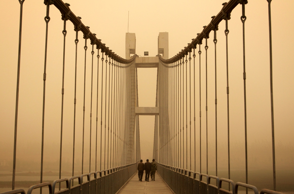 A sandstorm descends on a bridge in Ningxia Province, bringing life to an almost standstill. 2009