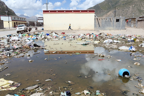 A boy walls past a polluted waterway in Zaduo, in the far interior of the Tibetan Plateau.