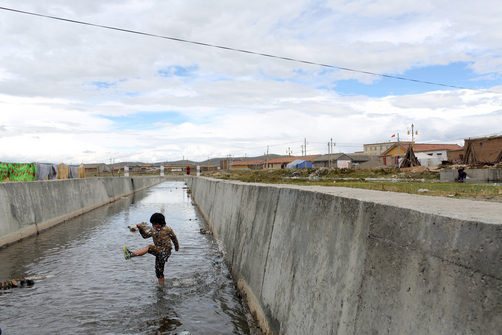 A young boy plays in a water channel in a small town on the Tibetan Plateau.