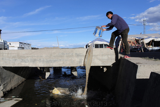 A man pours waste water into a polluted stream in the town of Sershul, Sichuan Province. 2012