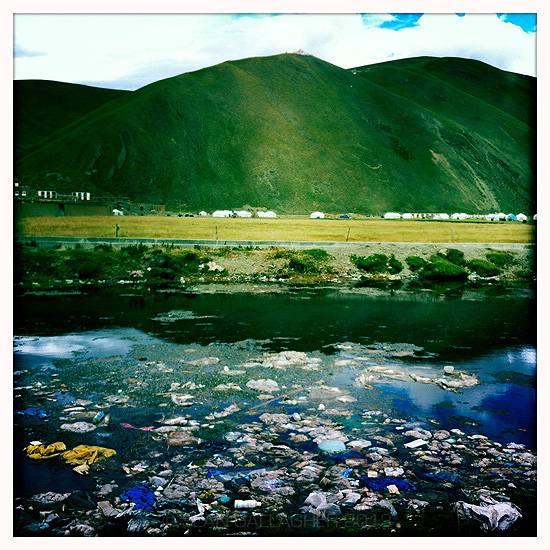Refuse gathers on the surface of a pond in the worn of Sershul, in Sichuan Province. 2012
