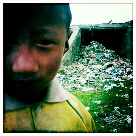 A Tibetan boy stands near to  a waterway that has been completely clogged by refuse in a town on the Tibetan Plateau. 2012