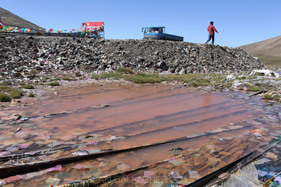 A pool of water is stained a red/orange colour from pollution on the Tibetan Plateau. 2012