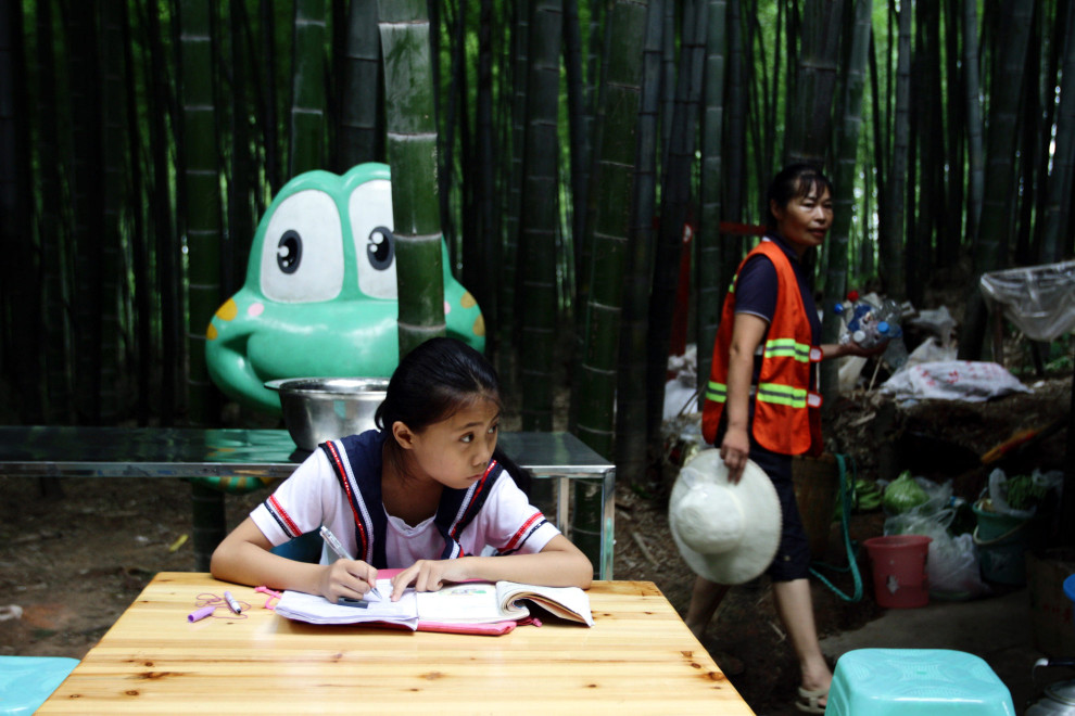 A schoolgirl does her homework in a community nestled within the forest.