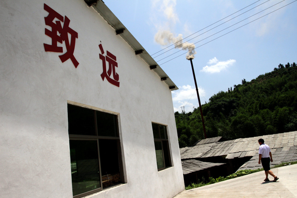 Smoke billows from a chimney in a bamboo factory in southern Sichuan. The factory produces furniture and chopsticks made from bamboo.