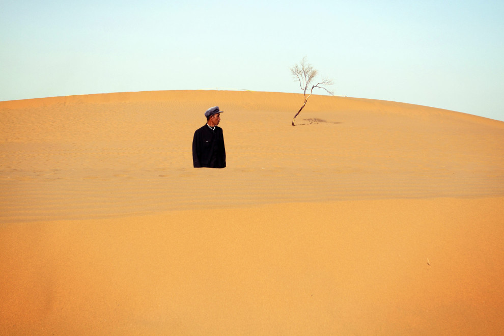 A man walks amongst the dunes of the Tennger desert, near the Shapotou desert resort in Ningxia Province.