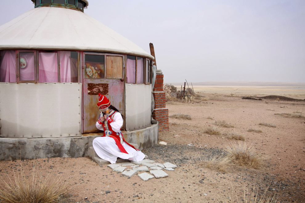 Faint glimpses of traditional life on the grasslands remain as a tourist in traditional dress adjusts her clothing.
