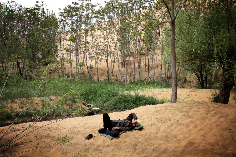 A worker sleeps amongst the sand dunes and forest at the Shapotou desert resort in Ningxia Province.