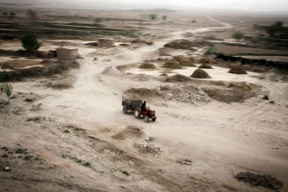 A tractor drives through dry and barren lands in Gansu Province, China.
