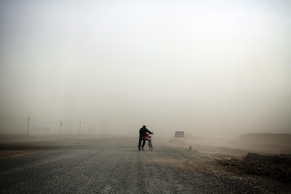 A man pushes his bicycle through a severe sandstorm on the outskirts of the town of Hongsibao, in Ningxia Province.