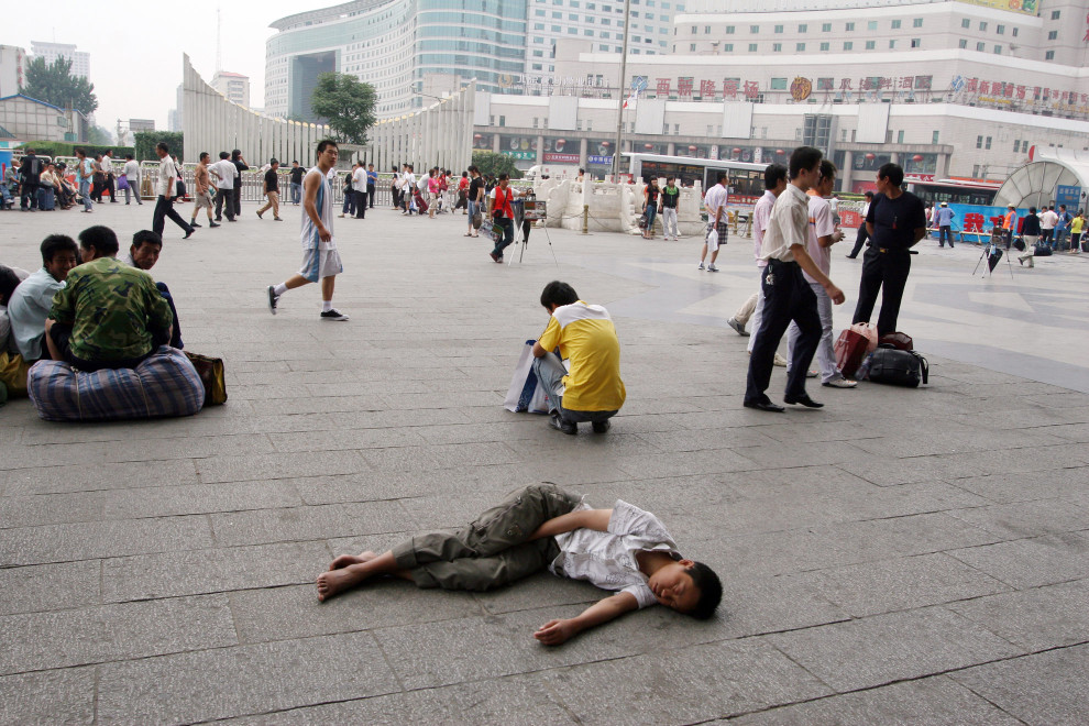 A man sleeps in fron of Beijing West train station.