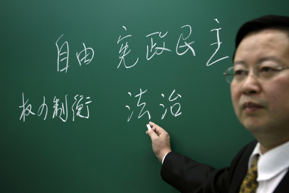 Professor Xia Yeliang from the school of Economics, at Peking University. On the blackboard it reads 'Freedom' (top-left), 'Constitutional Democracy' (top-right), 'Checking Balance' (bottom-left) and 'Rule of Law (bottom-right). For Der Spiegel.