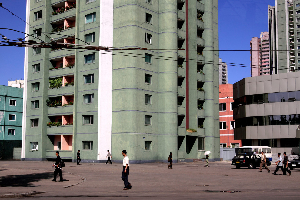 North Koreans walk past an apartment building in central Pyongyang.