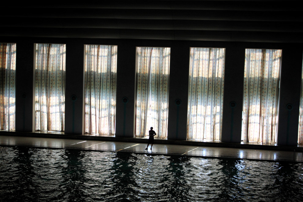A man stands next to a swimming pool in the Mangyongdae Children's Palace, an opulent after-school center for the children of North Korea's elite in Pyongyang.
