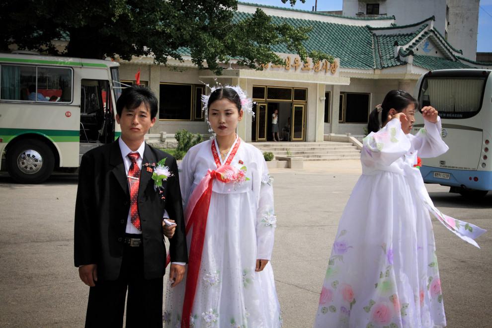 A bride and groom stand in a parking lot, in a small town near Pyongyang.