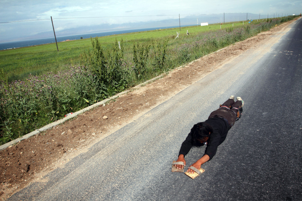 "Tenzin (27), a young Tibetan man prostrating around Qinghai Lake. The lake is sacred to Qinghai Tibetans and according to Tenzin, ""by circling it seven times, we can clear our sins and wrongdoings."""