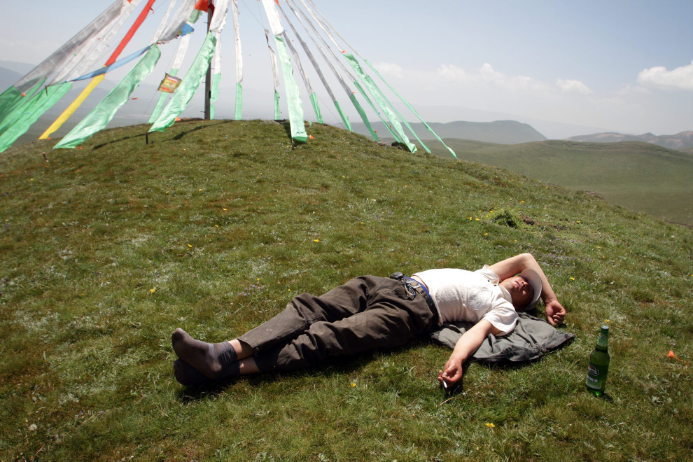 A tourist sleeps on the highland grasslands near Qinghai Lake.