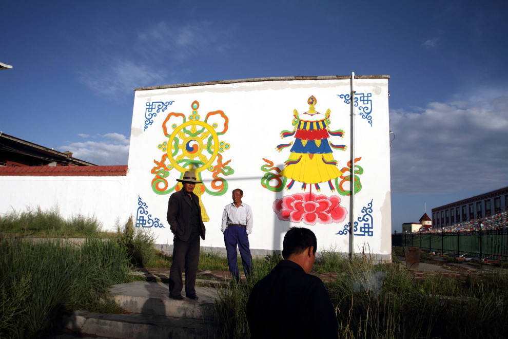 Tibetan men stand near a elaborately painted wall in a village near Qinghai Lake.