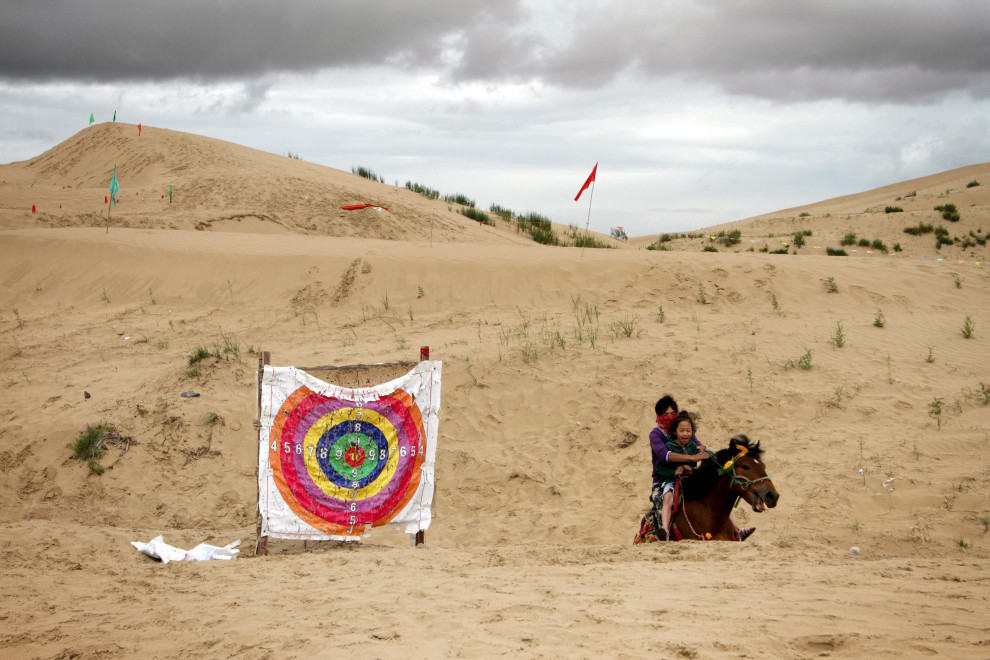 Tourists ride a horse through sand dunes near Qinghai Lake. Desertification is becoming an increasing problem on the Tibetan Plateau.