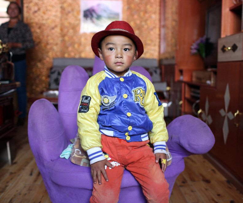 A young Tibetan boy in his home in a relocation village in the Amdo region of the Tibetan Plateau.