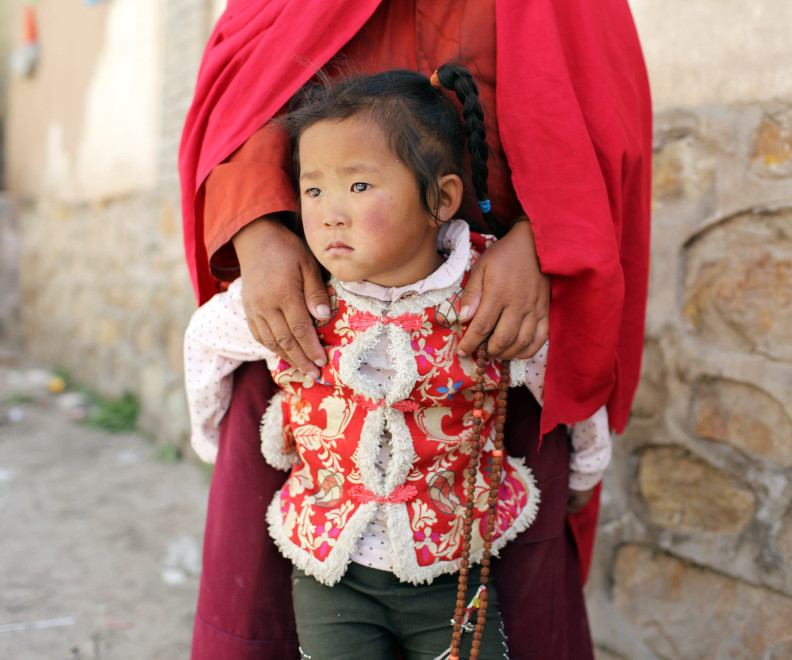 A young Tibetan girl is held by a female monk in the Amdo region of the Tibetan Plateau.