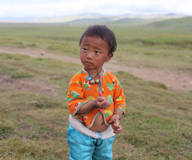 A Tibetan child on the grasslands in the Kham region of the Tibetan Plateau.