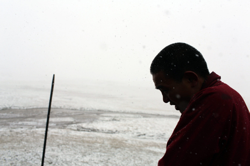 A Tibetan monk walks through a snowstorm in August. Snowstorms are rare at this time of year on the Tibetan Plateau, but climate change is leading to more extreme weather occurring at unexpected times.