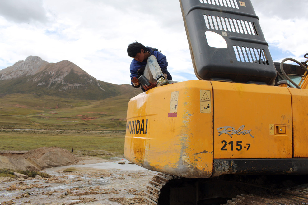 """A heavy-machinery operator takes a break. Construction in the region is increasing rapidly as the government implements its """"western development strategy,"""" aimed at bringing prosperity to the region."""