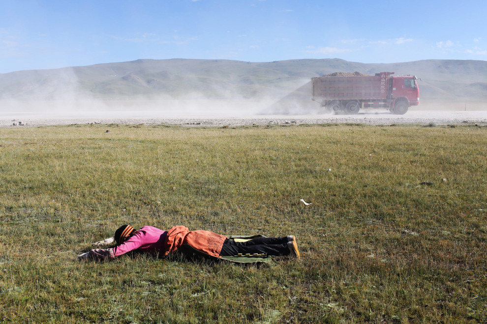 A Tibetan pilgrim prostrates himself during a pilgrimage to Lhasa.