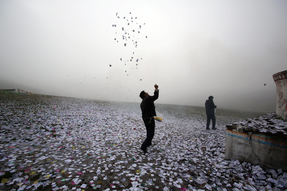 "A Tibetan man throws small pieces of paper, called ""wind horses,"" into the air, next to a stupa on top of a mountain on the Tibetan Plateau. This practice is is said to bring good luck and a safe journey.."
