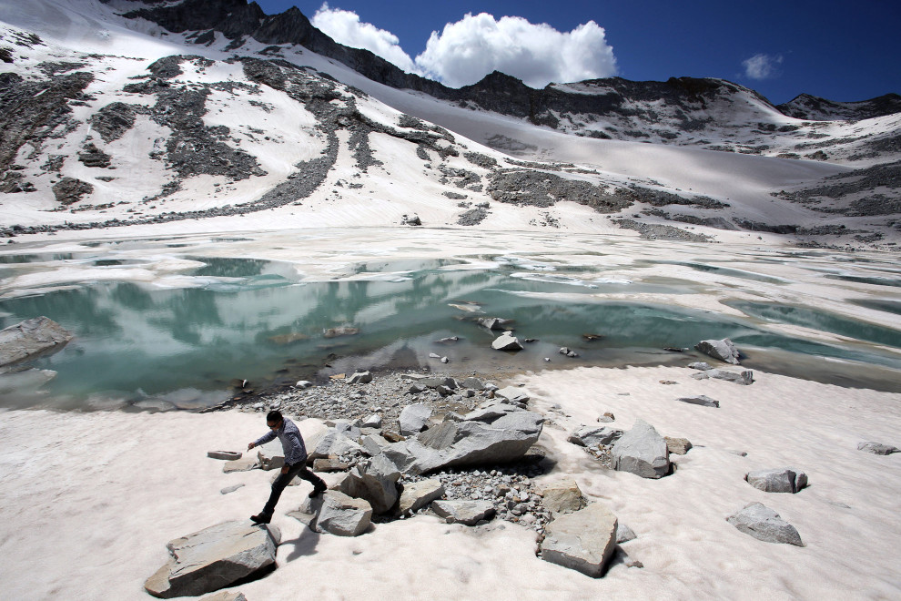 A man walks over rocks near to a glacial lake that has formed at the base of the Dagu Glacier, which lies at 5,100 metres on the Dagu Snow Mountain, on the south-east edge of the Tibetan Plateau.