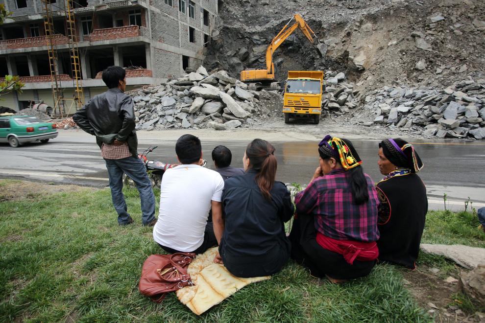 Local Tibetans watch as heavy machinery tears down the side of a mountain to make way for new homes and developments.
