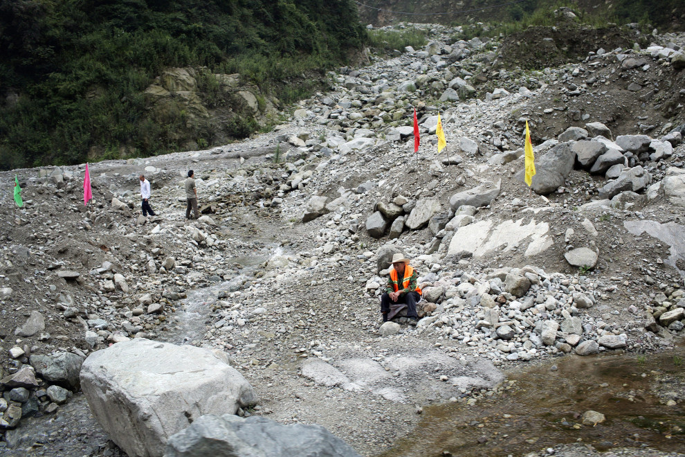 Construction workers sit among a rock field caused by flooding and landslides in the mountains of northern Sichuan, on the south-east edge of the Tibetan Plateau.