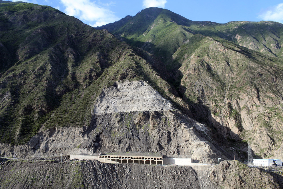 The side of a mountain has been cut away to allow for the building of a road that leads to the Maoergai Dam. Large-scale damming projects have caused knock-on environmental effects that have altered the local landscape forever.