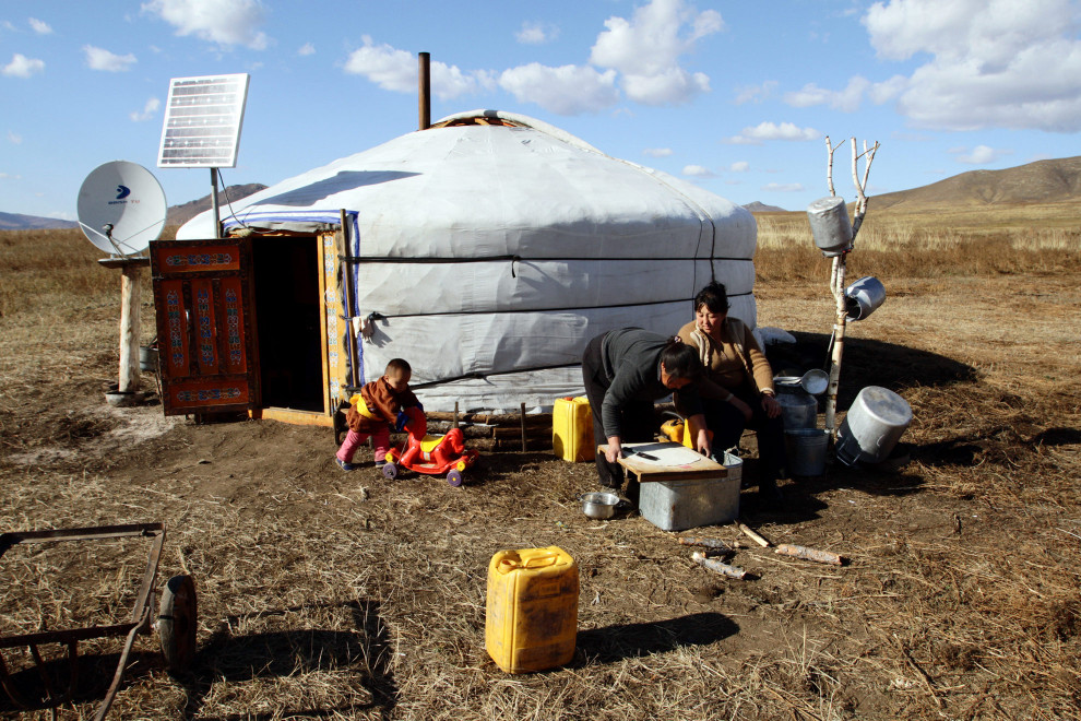 Local women preparing food outside a traditional Mongolian yurt and local people, near the Altansumber Forest.