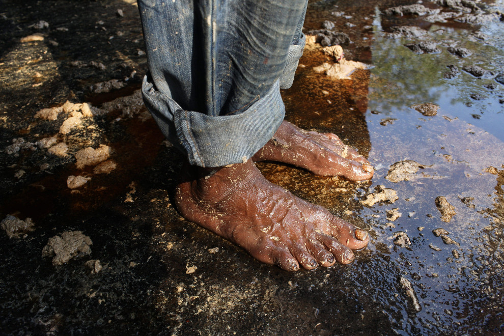 A tannery worker stands barefoot in an area used to collect waste waster from the dyeing and tanning process. The water is laced with a myriad of dangerous chemicals that are released into the local sewer system once used.