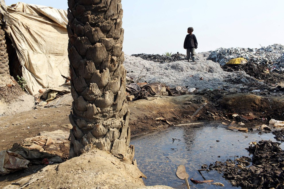 A young boy walks amongst discarded leather trimmings in a dumping ground on the banks of the Ganges River in Kanpur.