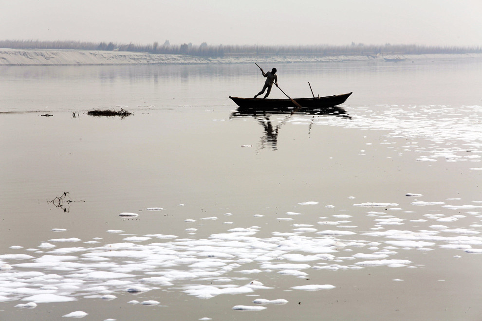 A fisherman pushes his boat along the Ganges River. Waste water in the foreground from nearby tanneries has contributed to the severe degradation of local water resources near the city of Kanpur.