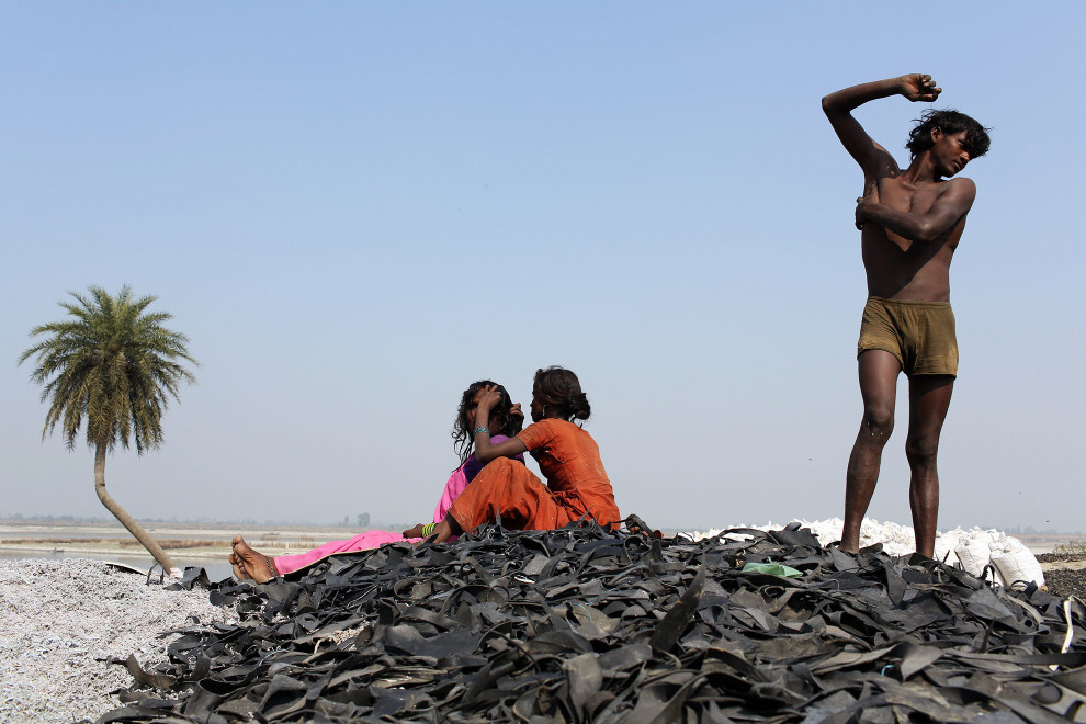 A family relaxes on top of a pile of leather trimmings at a dumpsite on the outskirts of the city of Kanpur. The trimmings are discarded from the nearby tannery factories and burnt, dried and then re-used as fertiliser and chicken feed.