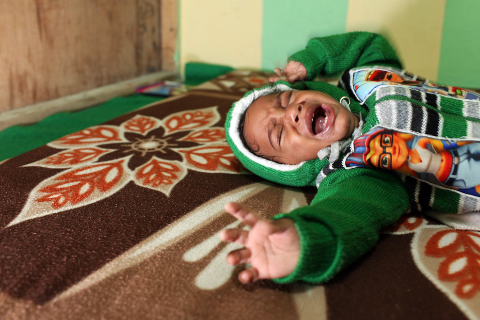 A young child screams in pain during a yoga session, as part of therapeutic treatment at the Baba Farid Center for Special Children in Faridkot, Punjab.