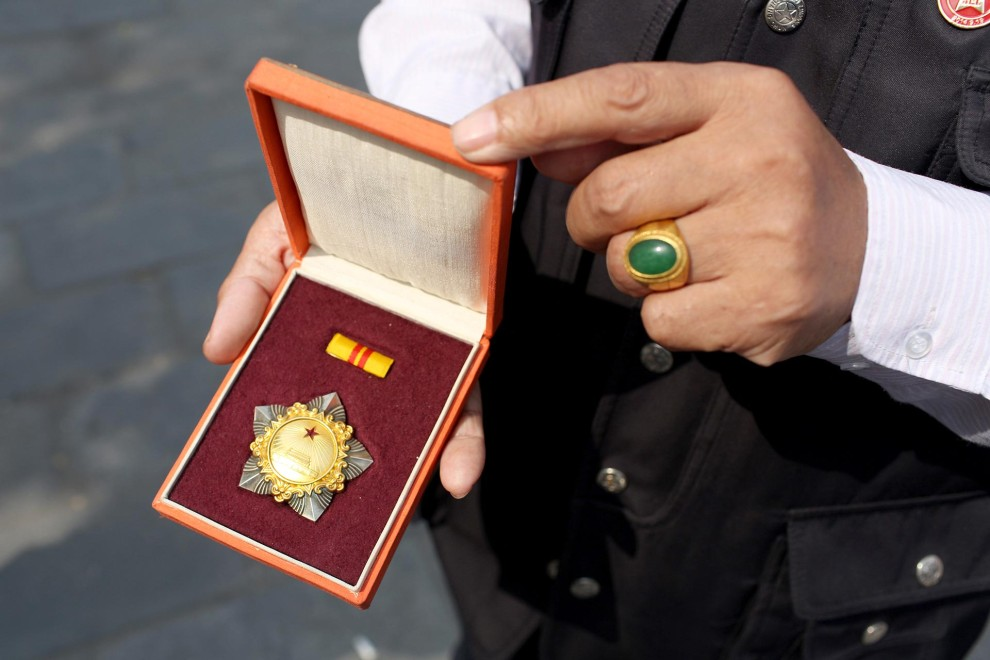 Yin Xijiang, a professional antiques collector, holds a 1995 medal given to second major generals in the Chinese army. The medal is worth 42,000 Chinese Renminbi (approx. 4000 Pounds Sterling) and is on display at a 'Red Memorabilia' show and sale, displaying items associated with Mao Zedong, the Communist Party and the Cultural Revolution, held at the Panjiayuan antiques market in Beijing, China.