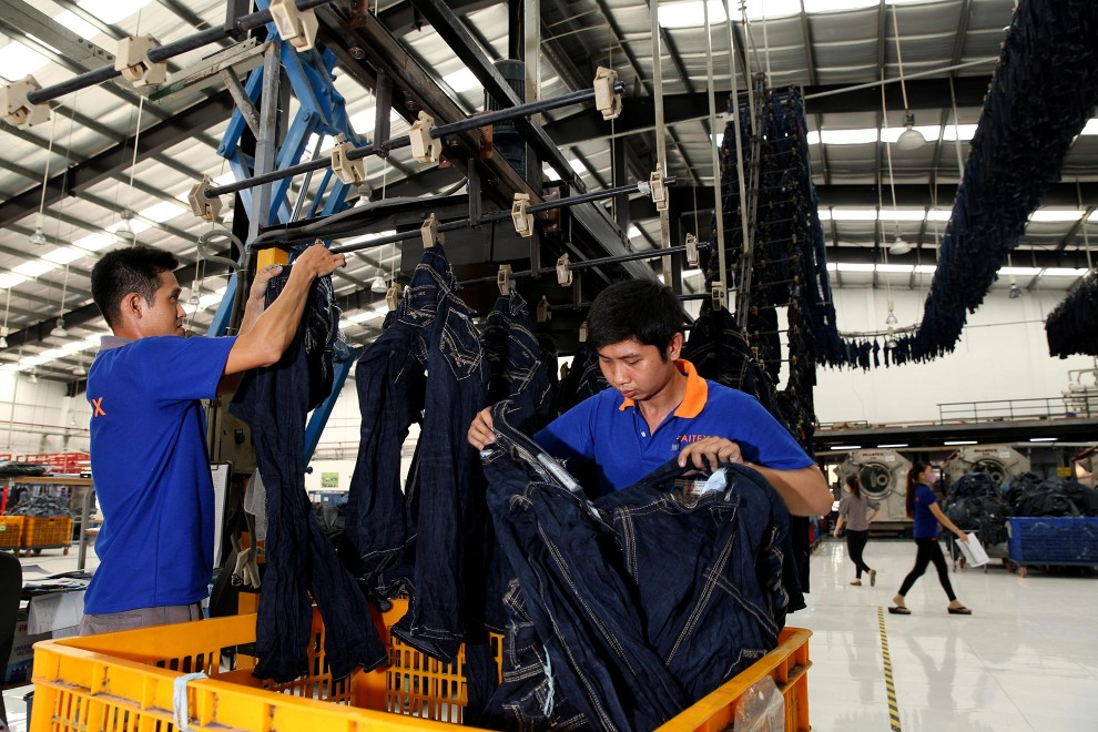 Workers hang jeans onto a large conveyor belt that naturally dries items at denim detailing company, Sai-Tex.