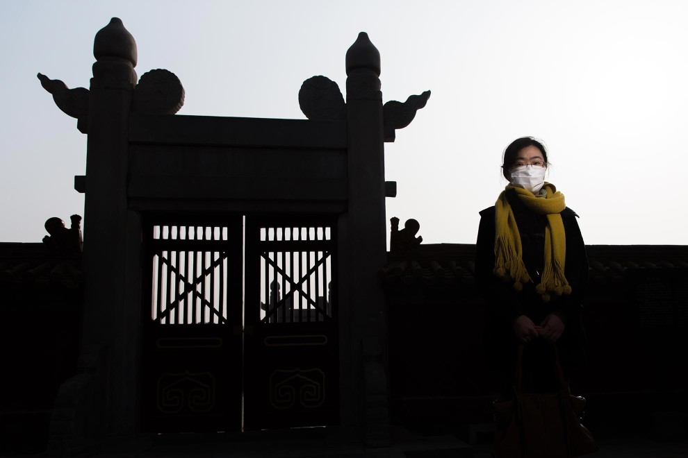 "Miss Song (30), from Dongbei Province, stands near an ornate gate in Beijing's Ditan Park. ""It's very dirty here. I started using the mask last year. From the year before last, China started to get this pollution. Pollution was a very new word for me. At that time, we started to know more about ""2.5"". My family don't wear masks. I suggested they use them but they didn't do it."" - PM2.5 reading - 365 - Hazardous"