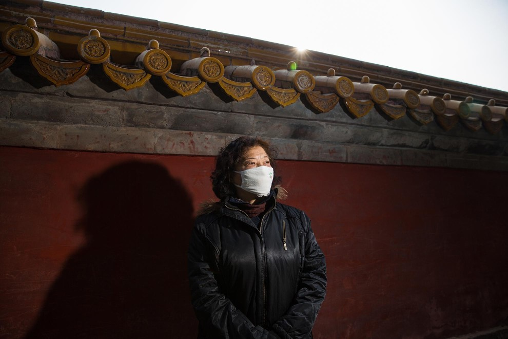 "Mrs. Zhang (62), a retiree in Beijing, stands near a wall in the capital's Ditan Park. ""Last year I bought a professional mask because I had a bad throat. The pollution made it worse. I think they are a bit strange looking. These past two years I've been wearing them. During the polluted days I definitely wear them. During the spring festival the pollution was really bad. I'm really scared of the pollution."" PM2.5 reading - 365 - Hazardous"