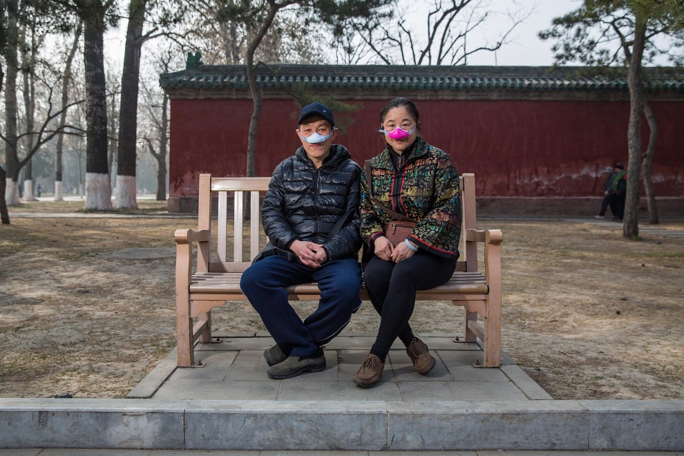 "Mr. Liu (56) and Mrs. Wang (54), a married couple in Beijing, sit on a bench in the capital's Ditan Park. Their unique pollution masks are designed to filter air breathed through the nose, with exhalation then from the mouth. They are one of the new types of masks now appearing as alternatives to the traditional face mask. ""We started using these one month ago"", explains Mr. Liu. ""This one is more comfortable. It filters out 95% of the pollution."" PM2.5 reading - 367 - Hazardous"