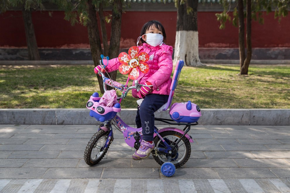 A young girl pauses for a moment while riding her bike through Beijing's Ditan Park. PM2.5 reading - 261 - Very Unhealthy