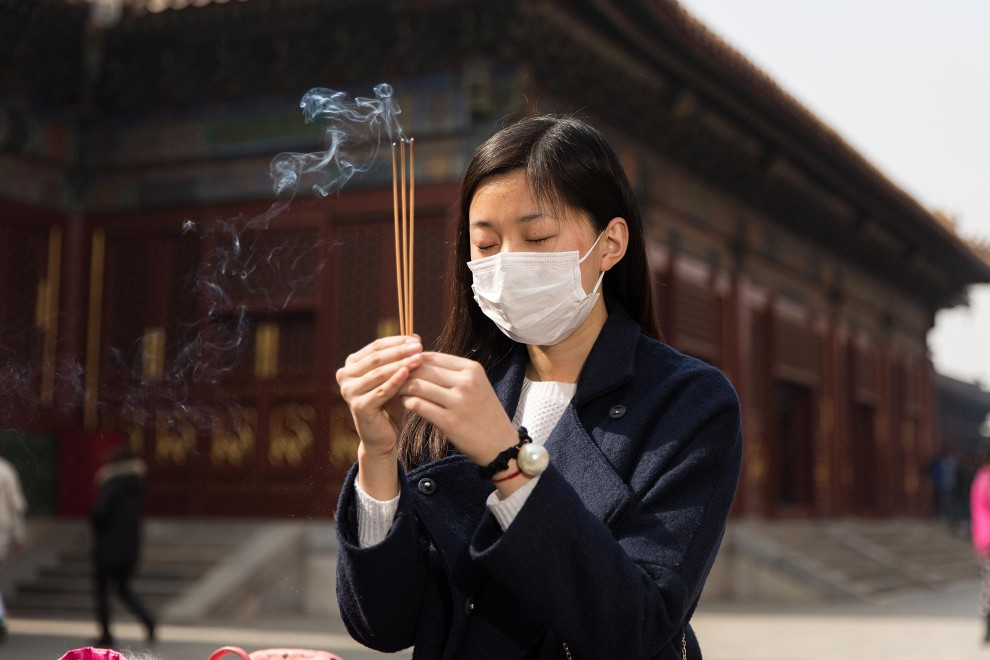 "Ms. Zeng (21), a student, burns incense while making wishes at a shrine inside Beijing's Lama Temple. ""I think the weather is bad. I started using the mask about one year ago because of the pollution."" PM2.5 reading - 261 - Very Unhealthy"