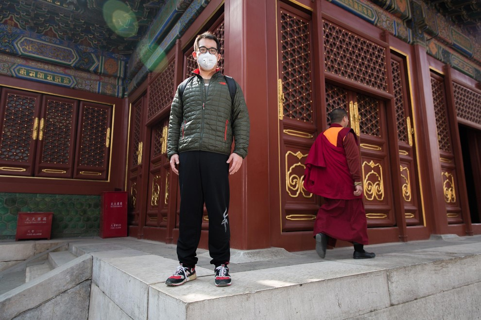 "Xue (29), an engineer visiting Beijing's Lama Temple. ""Of course it's not comfortable but we have to put it [the mask] on. I wore it earlier than most. I started about 4 years ago. I cough when I smell the dust."" PM2.5 reading - 200 - Unhealthy"