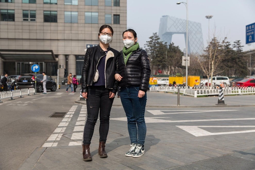 "Ms. Pan (left) and Ms. Zhu (right) are co-workers in an Environmental Landscape Design company in Beijing. ""The weather is too bad""' explains Ms. Pan. ""It's really uncomfortable. I can already feel the cough and headaches. In my professional area, we discuss [this issue] a lot. The air is getting worse and worse."" PM2.5 reading - 196 - Unhealthy"