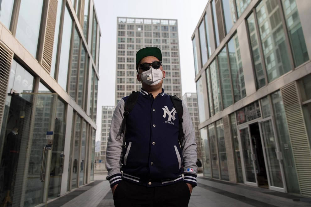 "Ren (27), a student and Beijing resident, stands in the cities modern CBD area. ""I started using the mask last year when the pollution got bad. I didn't pay much attention before that"", he explains. ""I don't like wearing it but I have to. I watched the [Chai Jing] documentary many times. I shared it with everyone. Now, I pay attention to our behaviour. The documentary inspired me. The future? It's hard to get the environment back. I'm thinking about emigrating."" PM2.5 reading - 184 - Unhealthy"